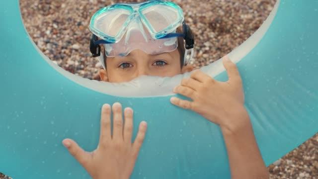 barn blåsa uppblåsbara cirkel. närbild av ung pojke förbereder gummi cirkel - inflatable ring bildbanksvideor och videomaterial från bakom kulisserna