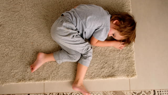Child is bored lying at home on the floor Sad little boy lying on the floor at home at the day time autism stock videos & royalty-free footage