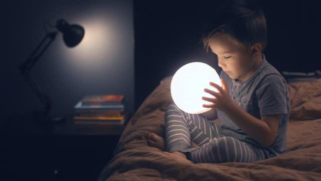 ett barn sitter på sängen och håller en glödande måne i händerna. - föreställningsförmåga bildbanksvideor och videomaterial från bakom kulisserna