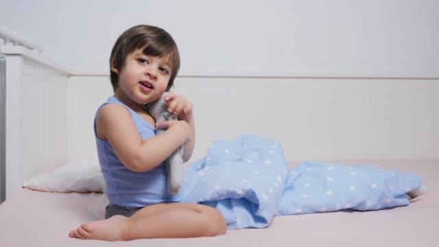 enfant est assis sur le lit dans un t-shirt et jouer - Vidéo