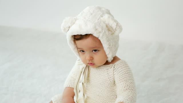 child is sitting on the bed in white clothes on white background - abbigliamento da neonato video stock e b–roll
