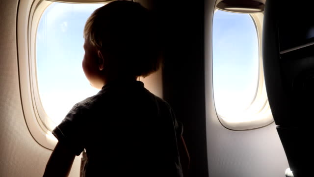 child is watching from the window of the porthole for the flight of the aircraft - neonati maschi video stock e b–roll