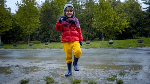 Child jumping in the rain for fun video