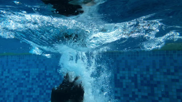 vídeos de stock e filmes b-roll de child jumping inside water pool - swim arms