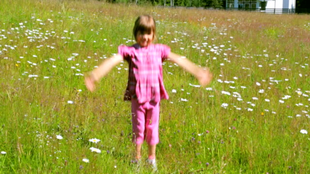 Child jumping on camomile field in summer morning video