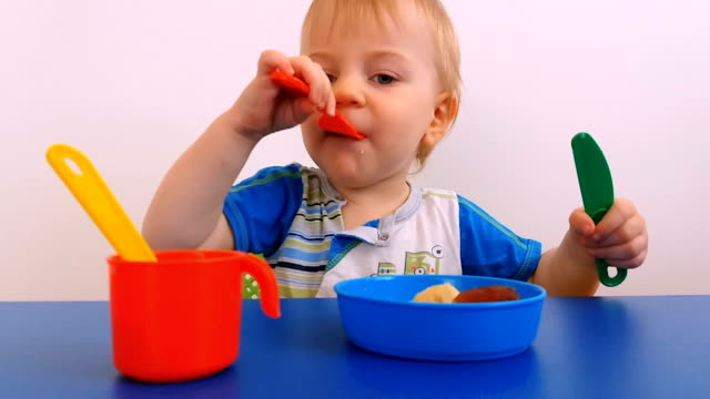 child learns to eat playing with toy dishes - solo neonati maschi video stock e b–roll