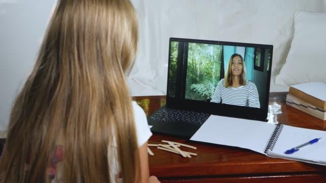 child little girl fa i compiti della lezione online a casa - didattica a distanza video stock e b–roll