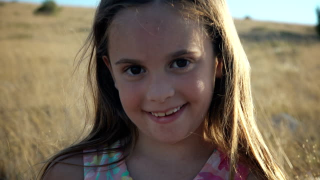 Child looking at camera, smiling, happy girl video