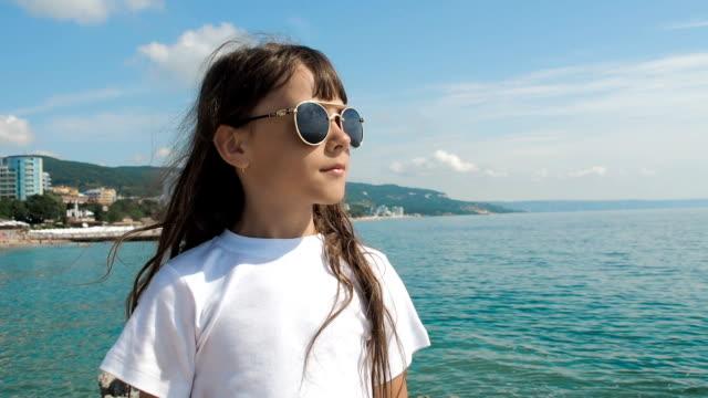 stockvideo's en b-roll-footage met kind dat op zee in zonnebrillen kijkt. - wit t shirt