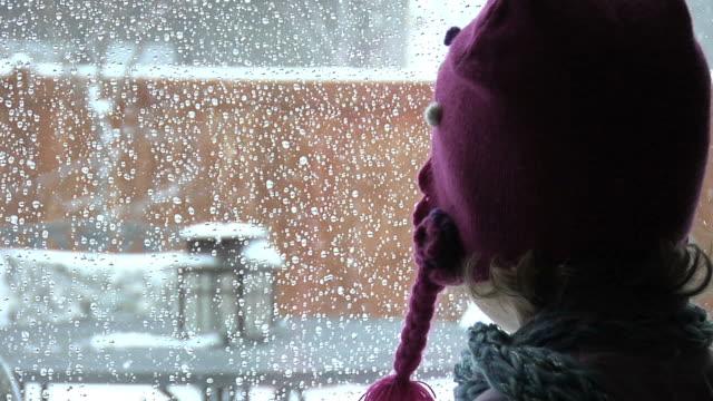 child looking out window - snow kids bildbanksvideor och videomaterial från bakom kulisserna