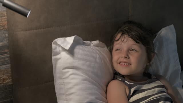 ett barn tittar på ljuset av en lampa. - endast flickor bildbanksvideor och videomaterial från bakom kulisserna