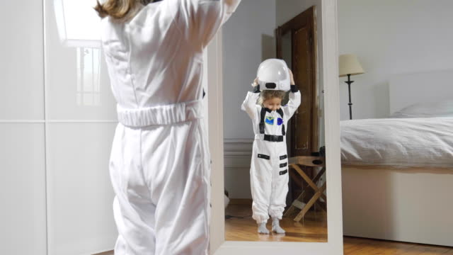 a child looks in front of the mirror wearing the astronaut's suit and looks great, his future, his job, his ambition to grow. - goals filmów i materiałów b-roll