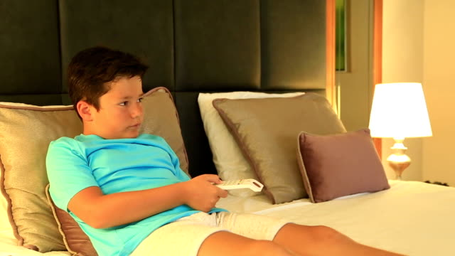 Child lying on a bed and watching cartoon in the bedroom video