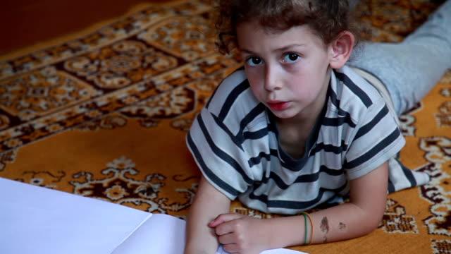 barn som ligger på mattan i vardagsrummet och ritning med blyertspennor - ligga på mage bildbanksvideor och videomaterial från bakom kulisserna