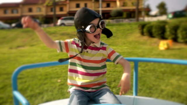 HD child on carousel in the park with aviator helmet video