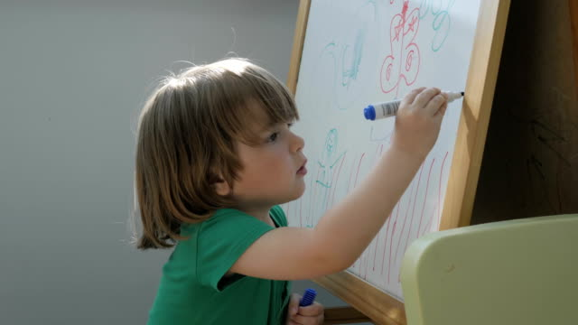 Child painting on easel. Closeup. Cute little boy is drawing with pencils in preschool. Child draw with colorful markers and smile.