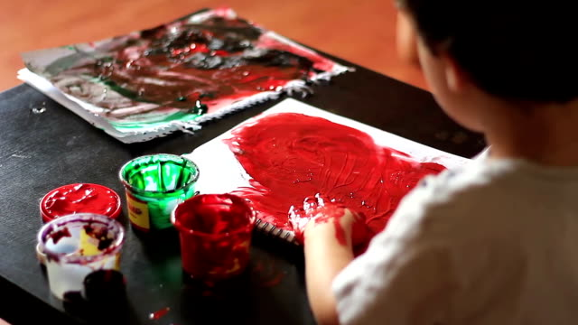 Child paints a sheet of paper by hand video