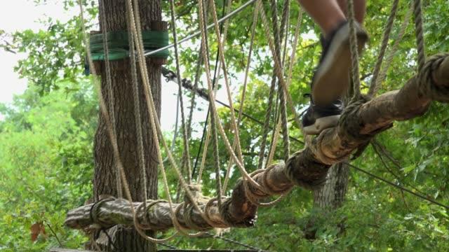 kind vorbei route im seilpark, sicherheit ausrüstung karabiner und seile zum klettern bäume in extremen park - ferienlager stock-videos und b-roll-filmmaterial