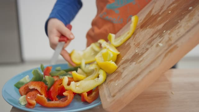 Child placing cut peppers onto a plate