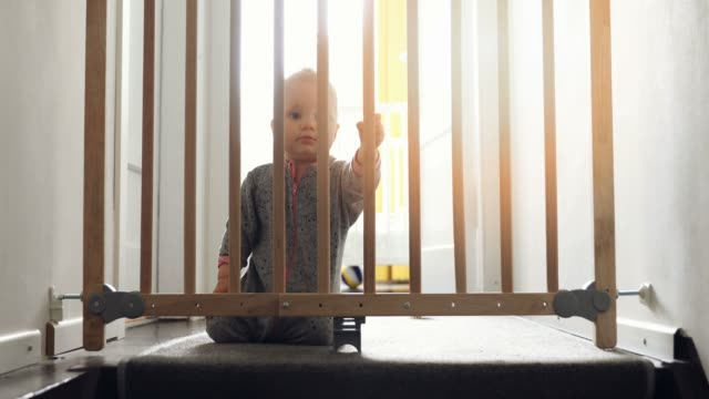 child playing behind safety gates in front of stairs at home video