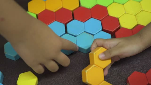 Child playing colored puzzle wooden block