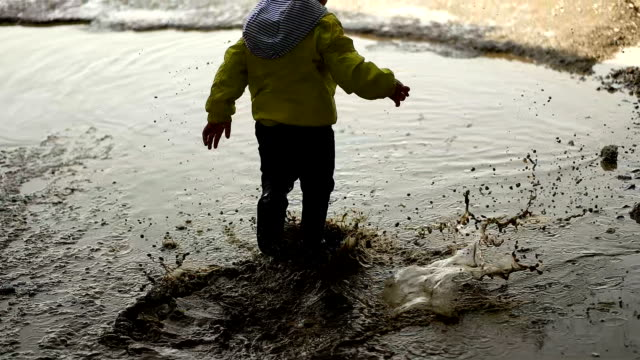 Child playing in muddy puddle Child playing in muddy puddle mud stock videos & royalty-free footage
