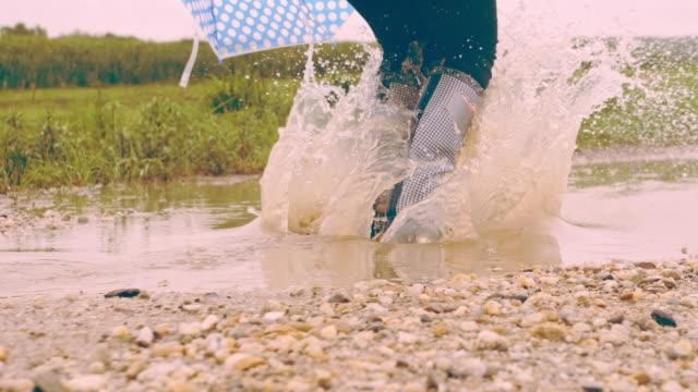 vidéos et rushes de slo mo enfant jouant dans la flaque d'eau boueuse - bottes