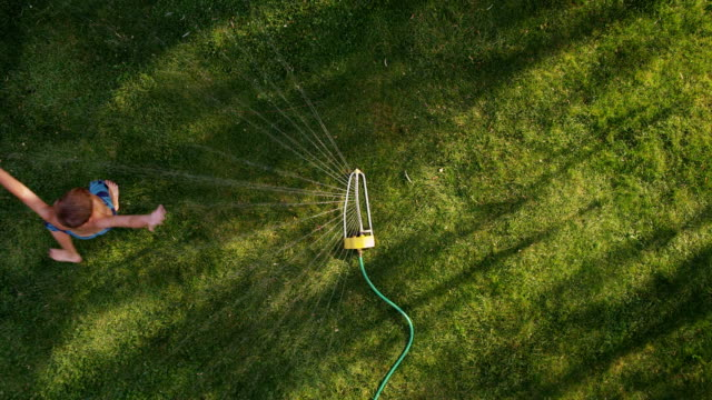 child playing in sprinkler, overhead shot - gräsmatta odlad mark bildbanksvideor och videomaterial från bakom kulisserna