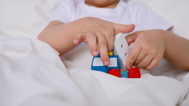 enfant jouant dans le jouet d'ambulance en bois de voiture sur le lit à la maison - Vidéo