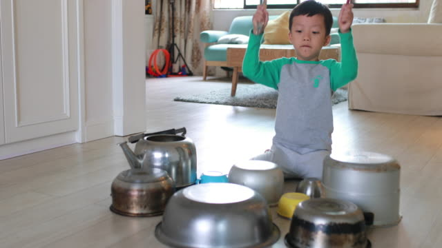 vídeos de stock e filmes b-roll de child playing on floor with pots and pans - instrumental