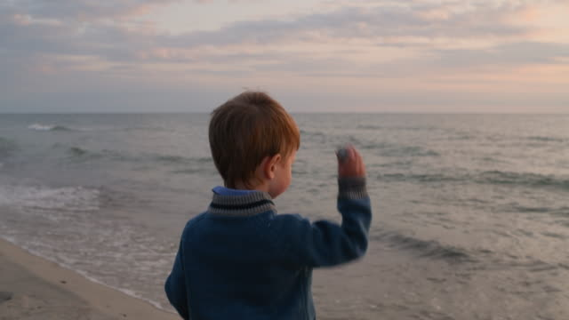 child playing on the beach in summer or autumn in sunset - solo bambini maschi video stock e b–roll