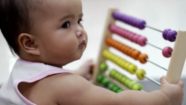 Child playing the abacus multi colored kid toy.