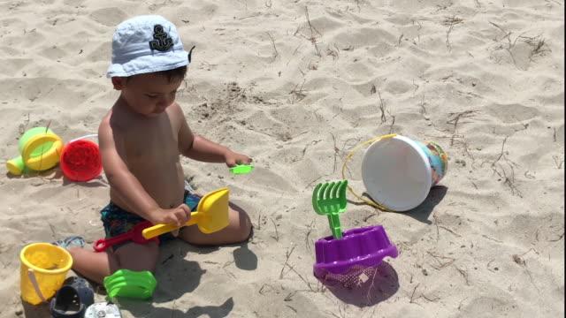 Criança que joga com cubeta e pá na praia - vídeo