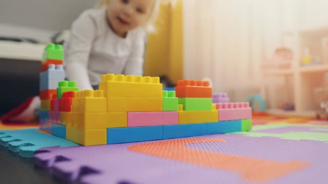 child playing with building blocks on the floor at home