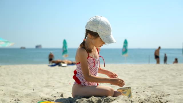 vídeos de stock, filmes e b-roll de criança brincando com areia na praia - boné