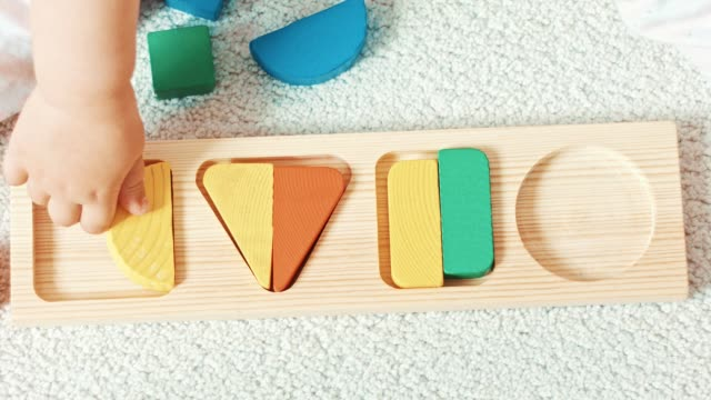 child plays with wooden toy baby sorter with geometric figures. top view - semplicità video stock e b–roll