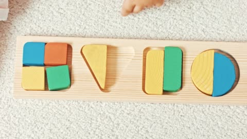vídeos de stock e filmes b-roll de child plays with wooden toy baby sorter with geometric figures. top view - claro