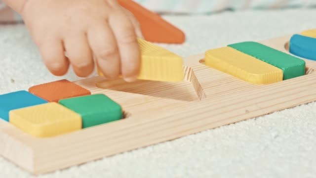 child plays with wooden toy baby sorter with geometric figures - semplicità video stock e b–roll