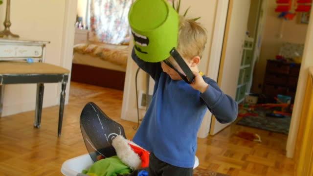 child puts felt bucket on his head - feltro video stock e b–roll