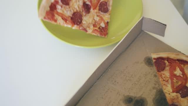 stockvideo's en b-roll-footage met het kind zet grote pizzaplakje op plaat close-up hogere mening - dikke pizza close up