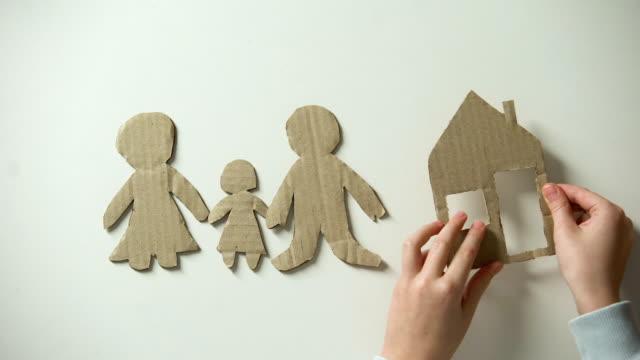 vídeos y material grabado en eventos de stock de niño poner casa de papel y corazón a la figura familiar, huérfano busca hogar - servicios sociales