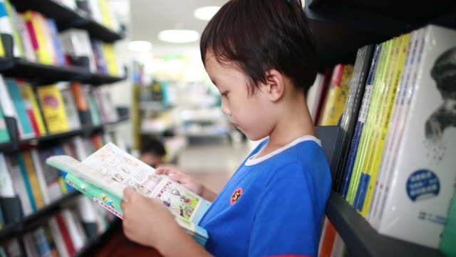 Child reading a book in the library Child reading a book in the library elementary age stock videos & royalty-free footage