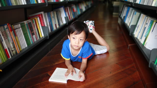 child reading a book in the library - letteratura video stock e b–roll