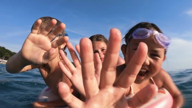 barn avkopplande i havet på sommarlov - inflatable ring bildbanksvideor och videomaterial från bakom kulisserna