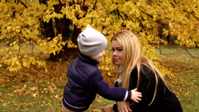 Child removes leaves from mother's hair in autumn. video