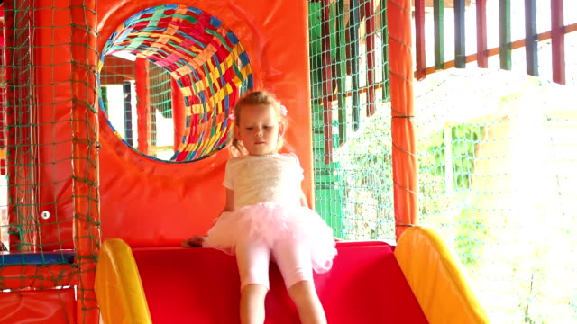 Child rides on a slide in a children's game room. video