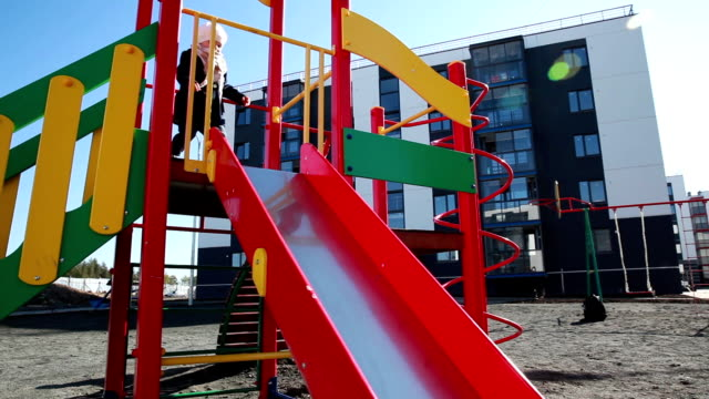 Child rides with children's slide at the city Playground. video