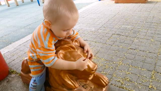 Child riding a lion sculpture video