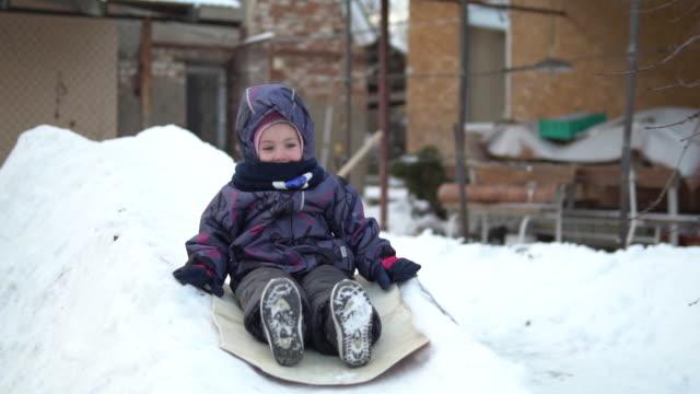 ett barn rullar på en snörutschbana. vinterkul på gatan. i den kalla vintern är barnet klädd i en jacka med en halsduk. slow motion - snow kids bildbanksvideor och videomaterial från bakom kulisserna