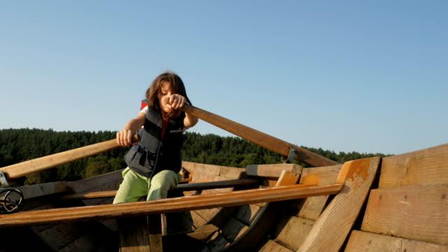 vídeos de stock, filmes e b-roll de criança remo os remos no barco - boia salva vidas